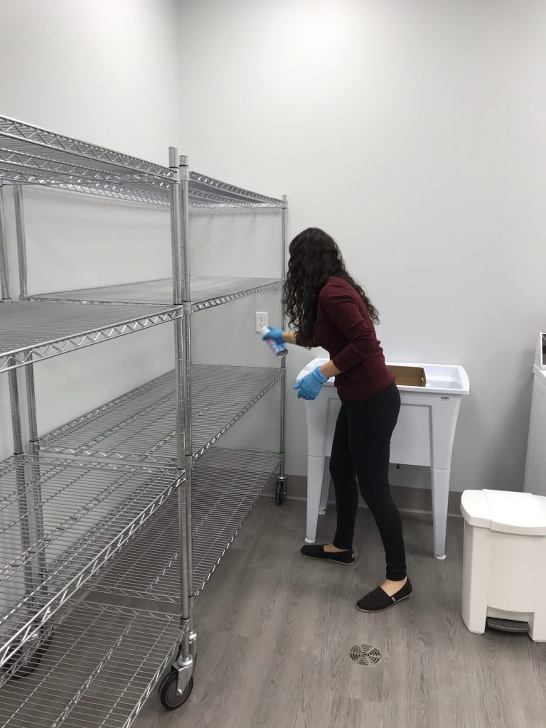 ESS staff member sanitizing storage racks inside the laundry and storage room of our Senior Care Centre.