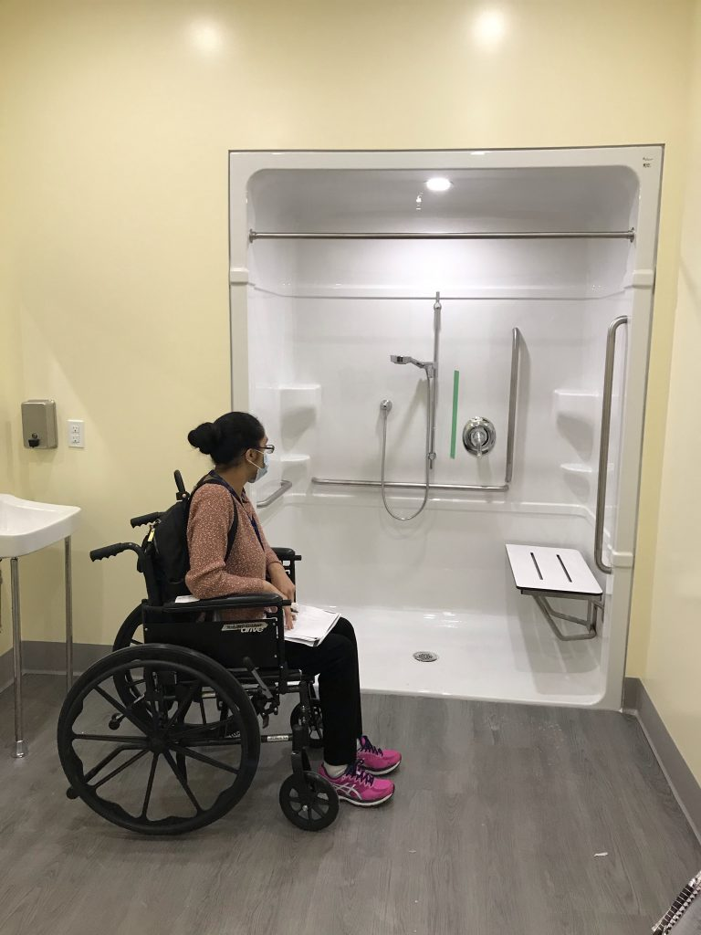 An occupational therapist is seated in a wheelchair to assess our washroom and shower room for accessibility.